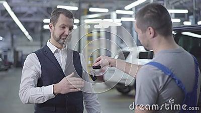 Ritratto di un uomo caucasiano con una barba adulta in completo elegante che prende le chiavi dell'auto dal meccanico e scuote la stock footage