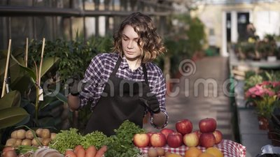 Ritratto di una bellissima contadina in guanti neri che preparano alimenti biologici al mercato agricolo in piedi all'interno di  stock footage