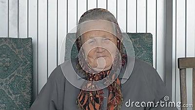 Ritratto di una donna anziana sorridente in una bandana marrone stock footage