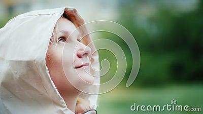Ritratto di una giovane donna, che si gode la pioggia primaverile, che guarda in alto Hockey e avventura, concetto di freschezza video d archivio