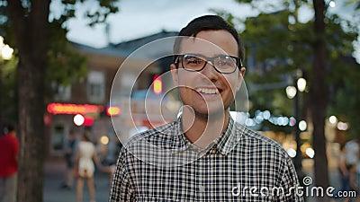 Ritratto di uno studente di bell'aspetto con gli occhiali che ride in strada di città la sera archivi video
