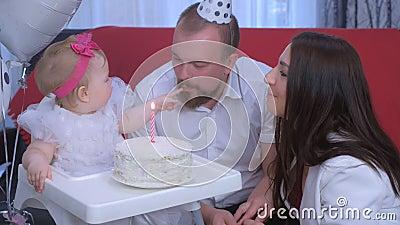 Ritratto familiare mamma, papà e bambina al primo compleanno con torta e candela video d archivio