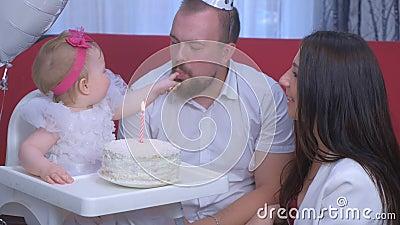 Ritratto familiare mamma, papà e bambina al primo compleanno con torta e candela stock footage