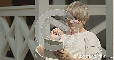 Ritratto senior della donna facendo uso della compressa con i vetri divertendosi all'aperto su Sunny Day al colpo di casa di cura stock footage