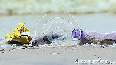 Riva sporca dell'oceano con il pesce morto, onde che prendono detriti e lettiera, ecologia archivi video