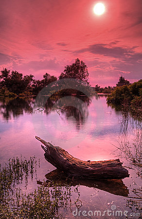 River landscape with red sky and sun