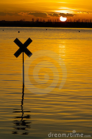 River marker silhouetted against the setting sun