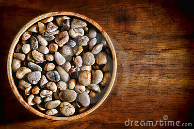 River Rock Pebbles in Wooden Bowl on Wood Plank