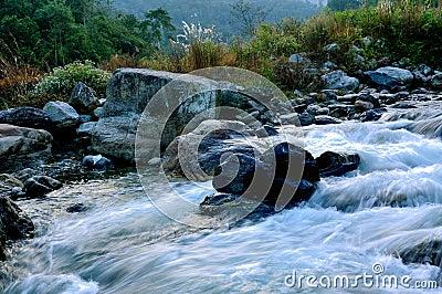 River water flowing through rocks at dawn