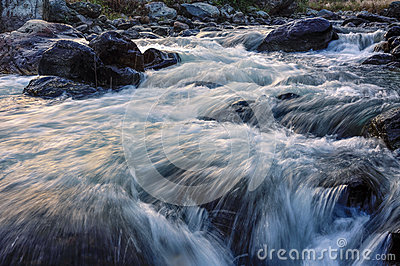 River water flowing through rocks at dawn