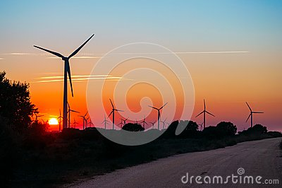 Road across sun and silhouettes of wind generators