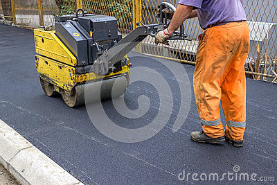 Road construction worker behind construction roller