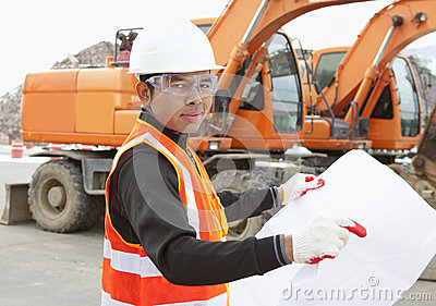Road construction worker in front of excavator