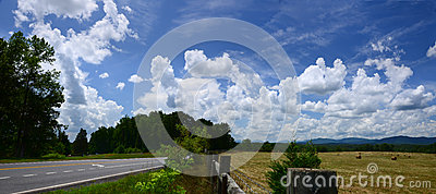 Road and Field Under Fluffy Clouds in Blue Sky