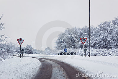 Road with give way signs in the snow