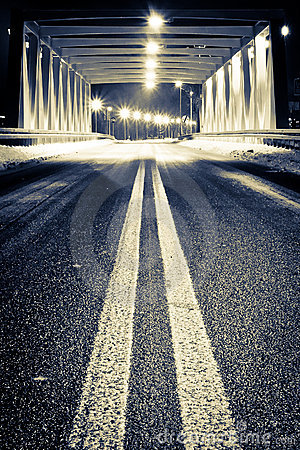 Road by illuminated bridge at night