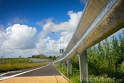 Road with protective metal side fence and sky