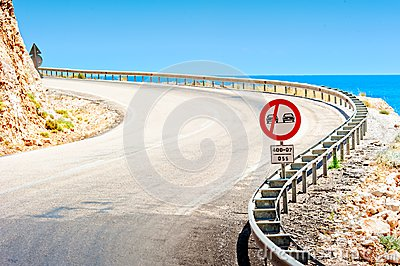Road sign and a mountain road along sea