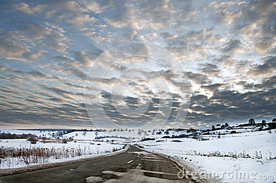 Road in winter with sun at sunset