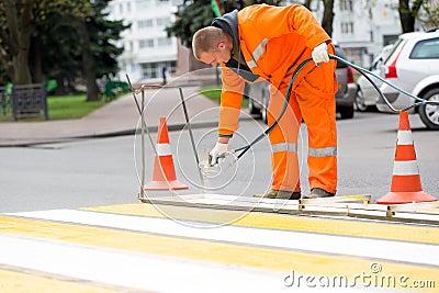 Road worker marking street lines zebra crossing Stock Photo
