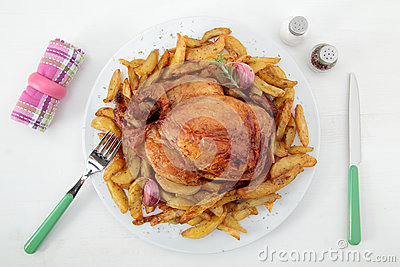 Roast chicken and potatoes on the white table