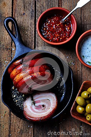 Free Roast Pork Belly Roll With Pepper, Sea Salt, Dried Rosemary, Basil And Garlic On A Wooden Table. Rustic Style. Royalty Free Stock Image - 63780846