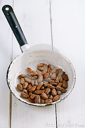 Roasted cocoa chocolate beans in pan on white wood table