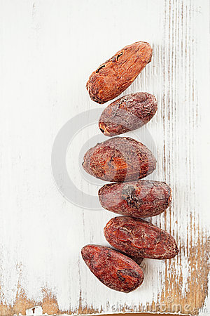 Roasted cocoa chocolate beans on white wooden background