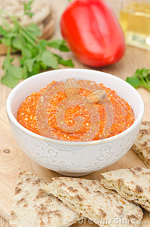 Roasted pepper dip with almonds and garlic in a bowl vertical