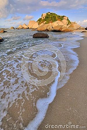Roca de la playa del mar bajo iluminación de la puesta del sol