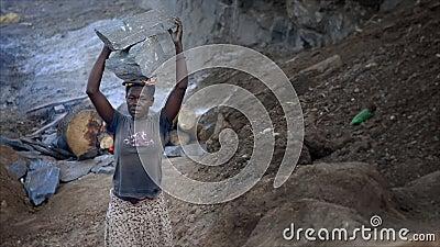 Roca que lleva de la mujer pobre en África almacen de metraje de vídeo