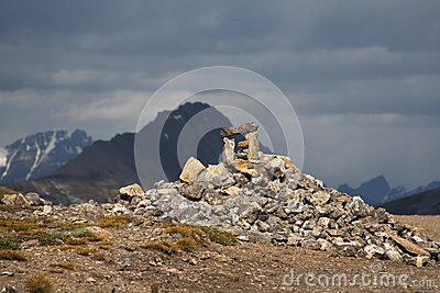 Rock cairn in sunlight on stormy day