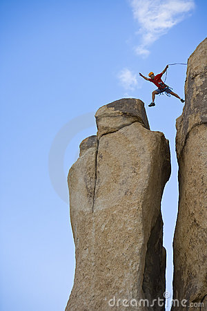 Free Rock Climber Jumping For The Summit. Stock Photos - 6437583