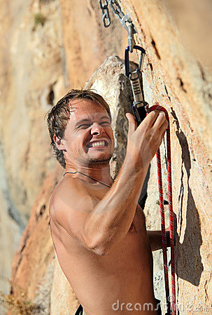 Rock climber struggling to fasten rope to quick-dr