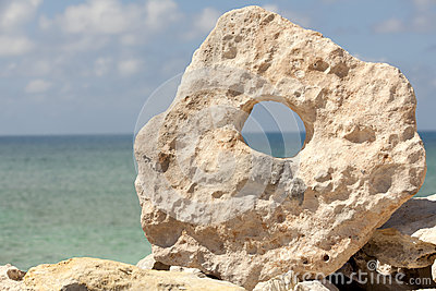 Rock with hole and ocean in the background