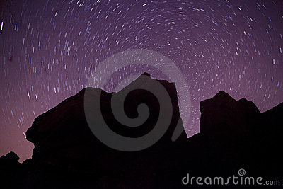 Rock silhouette and star trails round polaris