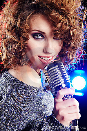 Rock star. Woman singing in retro mic