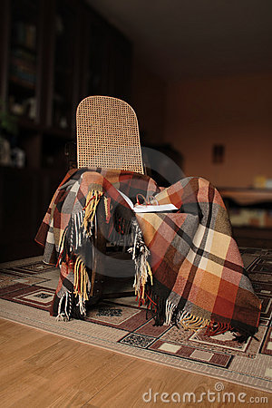 Rocking-chair with plaid and book