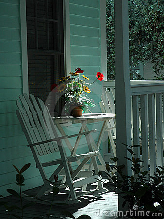 Table with a vase of flowers on a small porch in key west florida