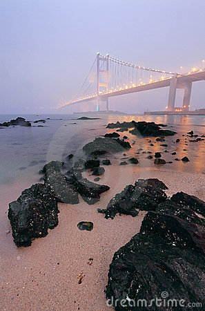 Rocks on the beach and bridge