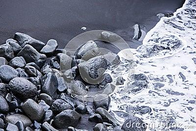 Rocks on the black sand and sea waves