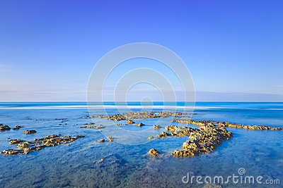 Rocks in a blue ocean under clear sky on sunrise.