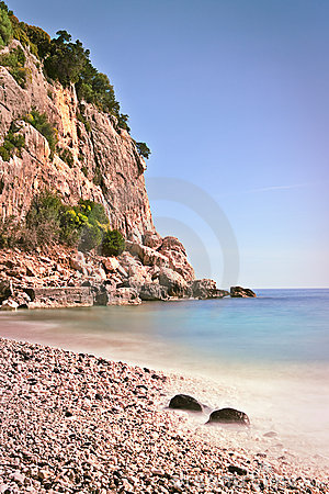 Rocky beach high cliffs blue sea