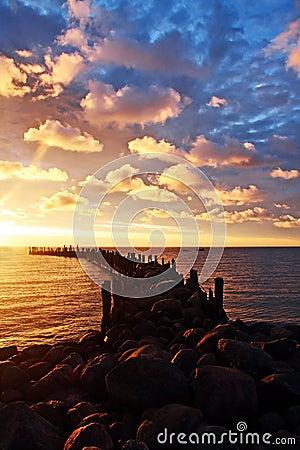 Rocky pier, sunrise, cloudscape
