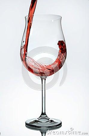 Rode wijn die in een wijnglas wordt gegoten