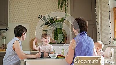 Rodzina homoseksualnych lesbijek z dwójką dzieci i matek siedzi w kuchni przy stole i je śniadanie Styl życia zdjęcie wideo