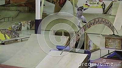 Rollenschlittschuhläuferdia vom vertikalen Sprungbrett, Rolle auf Bogen mit den angehobenen Händen Herausforderung im skatepark stock footage
