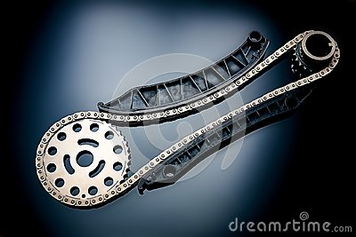 Roller chain with sprocket on dark background. It is used on cars, motorcycles, bicycles and in mechanical engineering. Stock Photo