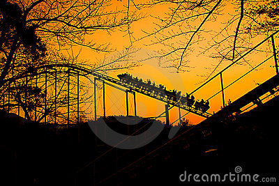 Roller coaster train is going up at autumn sunset