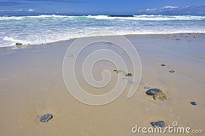 Rolling waves stones rocks on empty beach